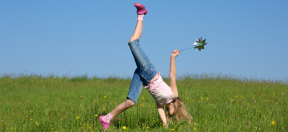 Girl doing a handstand on meadow